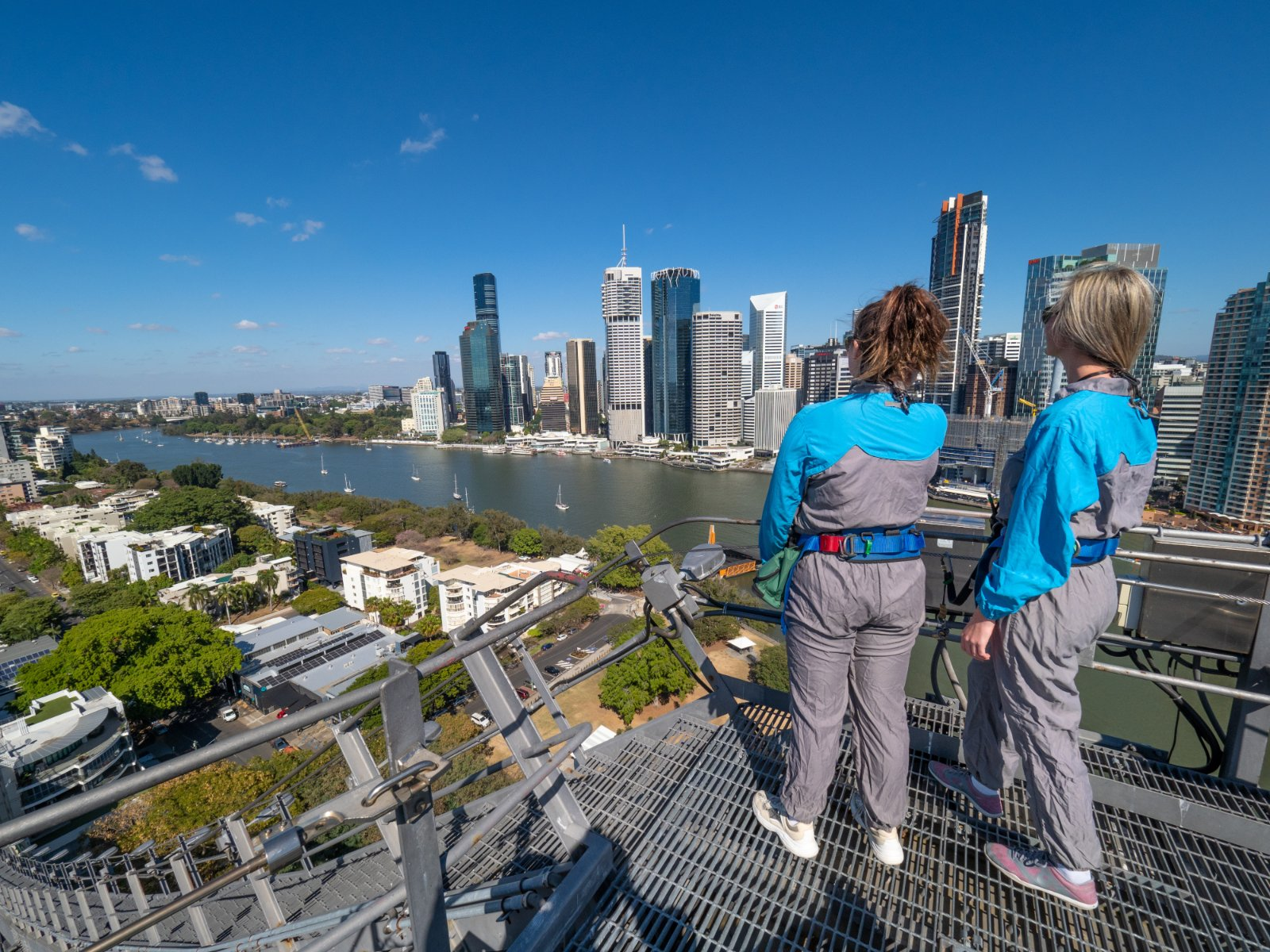 Two people standing on top of the Story Bridge looking towards Eagle Street Pier Brisbane on a Day Trip